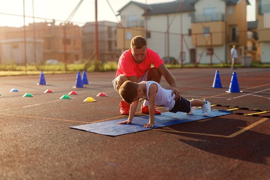 Trener pomaže malom sportisti da radi pravilno čučnjeve - deca i sport