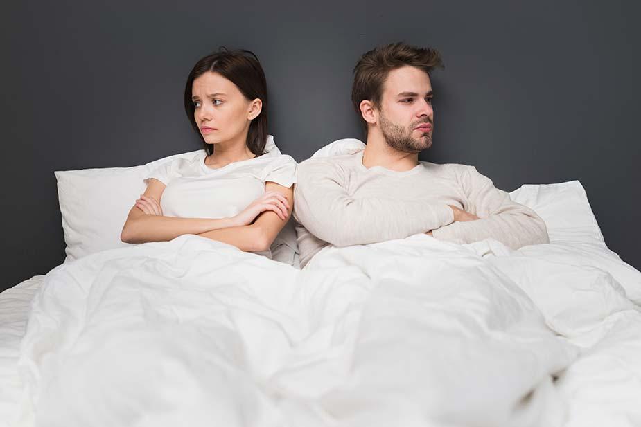 Par u krevetu neraspoložen, prekrštenih ruku gleda svako na svoju stranu - bolni seksualni odnosi