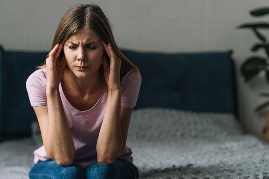 Žena sedi na krevetu i masira slepoočnice jer je boli glava